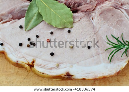 Smoked cured leg ham slice bay leaves, rosemary and pepper. - stock photo