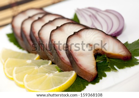 Smoked eel steaks served with lemon and celery on a plate - stock photo