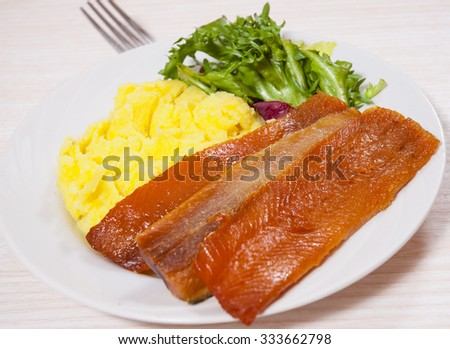 smoked fish fillet with mashed potatoes and salad - stock photo