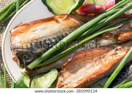 smoked fish with a variety of vegetables on a platter - stock photo
