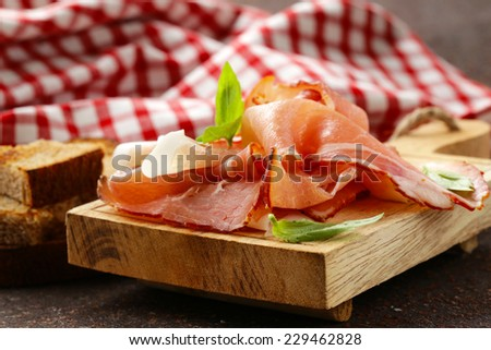 smoked ham jamon (Parma) with basil leaves on a wooden board - stock photo