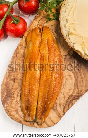 smoked herring fillet, slice of bread with butter, tomatoes and parsley on a wooden board