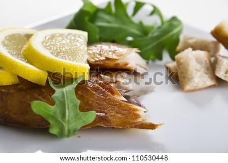 Smoked mackerel fish with lemon salad and bread - stock photo