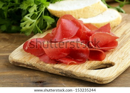 Smoked meat bresaola on a cutting board  - stock photo