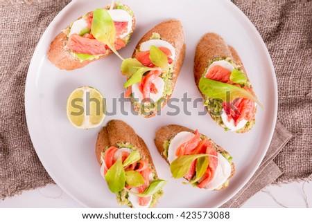 Smoked Salmon and Avocado Open-Faced Sandwich. Smoked Salmon Sandwich with Mozzarella. Smoked Salmon Appetizers. Avocado and Smoked Salmon Crostini  - stock photo