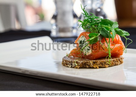 Smoked salmon and cream cheese arranged on white plate - stock photo