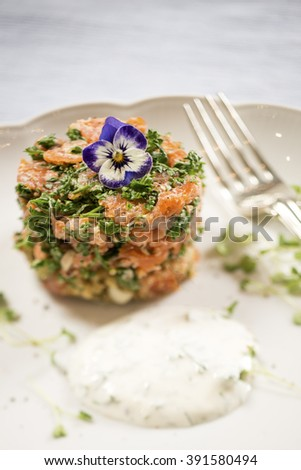 Smoked Salmon and Quinoa Cake with a Lemon and Dill Sauce, with a Lemon Wedge on a White Plate - stock photo
