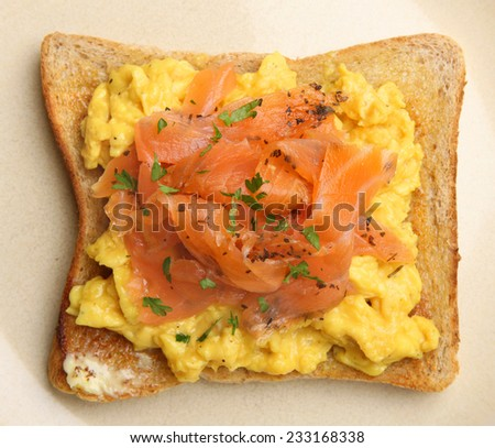 Smoked salmon and scrambled eggs on toast. - stock photo