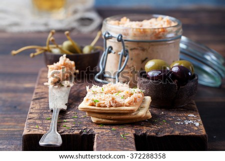 Smoked salmon and soft cheese spread, mousse, pate in a jar with crackers, olives and capers on a wooden background - stock photo