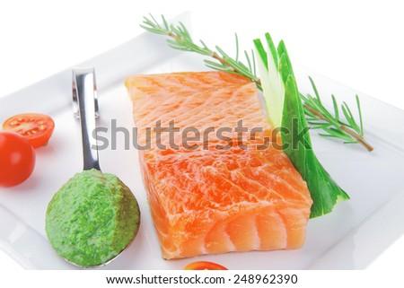 smoked salmon bar on plate with tomatoes and pesto sauce - stock photo