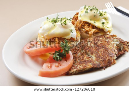 Smoked salmon eggs benedict served with tomato and hashbrowns. - stock photo