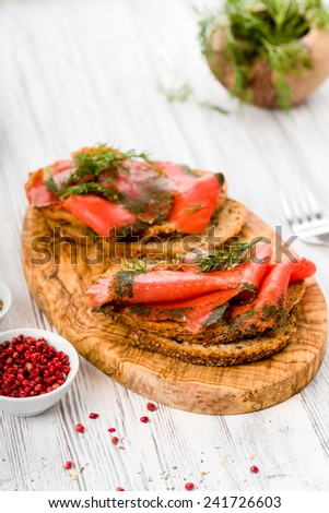 Smoked salmon marinated with fresh dill and spices on wooden board