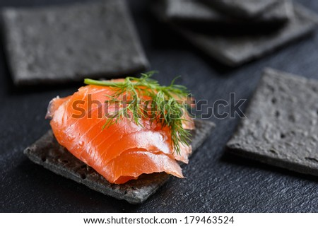 Smoked Salmon on charcoal crackers - stock photo