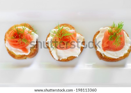 Smoked salmon or lox with cream cheese and dill on herb crostini - stock photo