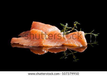 Smoked salmon pieces isolated on black background with fresh herbs. Culinary seafood. - stock photo