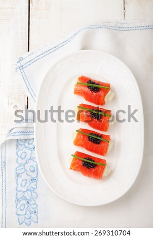 Smoked salmon rolls with cream cheese, cucumber, black caviar and chives - stock photo