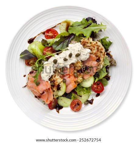 Smoked salmon salad with potato rosti and creme fraiche.  Overhead view, isolated on white. - stock photo