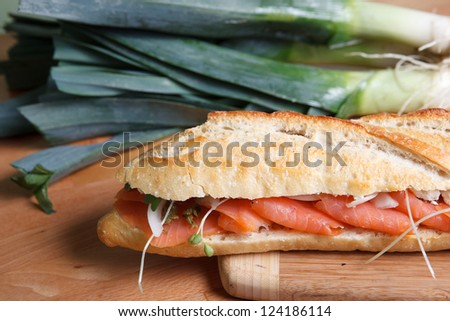 Smoked Salmon sandwich on baguette garnished with large green onions. - stock photo