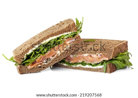Smoked salmon sandwich on rye with arugula, cream cheese and capers.  Isolated. - stock photo
