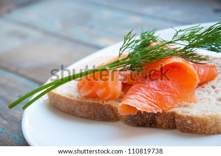 Smoked salmon served in freshly baked sourdough bread garnished with fresh dill. - stock photo