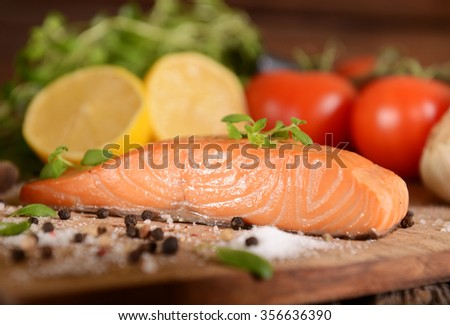 Smoked salmon slice on wooden board - stock photo