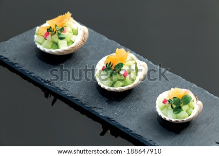 Smoked salmon snacks served in shells, slate plate on dark glass background