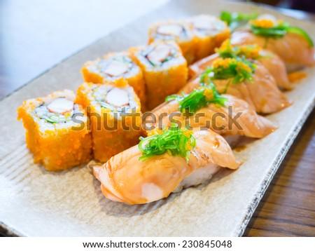 Smoked salmon sushi set on plate - stock photo