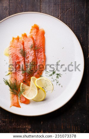 Smoked Salmon with dill and lemon on white plate - stock photo
