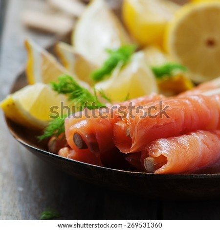 Smoked salmon with grissini and lemon, selective focus and square image - stock photo