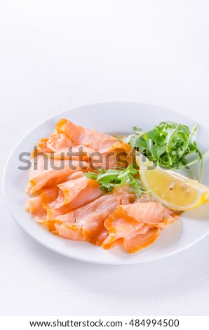 smoked salmon with lemon slices on white plate