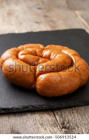 smoked sausage ring on black stone background