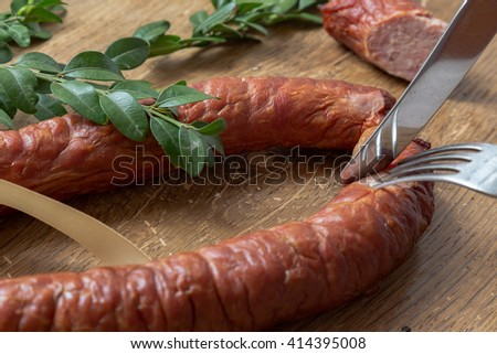 Smoked sausage ring with herbs in rustic style