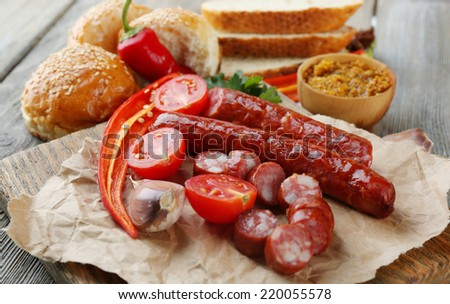 Smoked thin sausages and vegetables on cutting board, on wooden background - stock photo