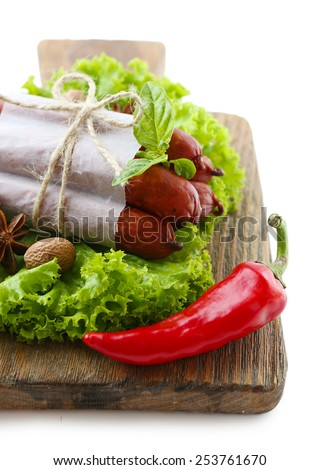 Smoked thin sausages  with lettuce salad leaves and spices on wooden cutting board, isolated on white