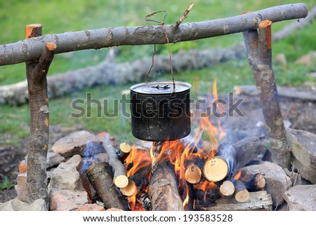 smoked tourist kettle over campfire  - stock photo