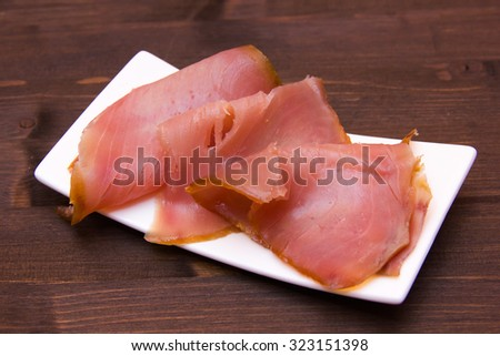 Smoked tuna on small tray on wooden table