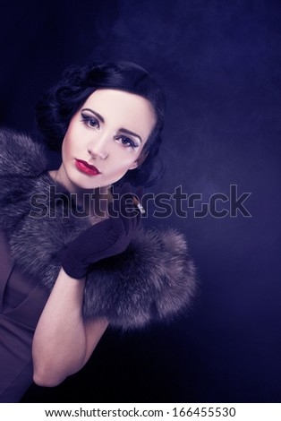 Smoker. Young woman in vintage image smoking cigarette. - stock photo