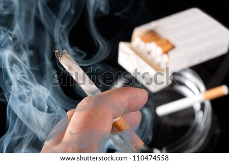 Smokers hand with ashtray and cigarettes pack on background - stock photo