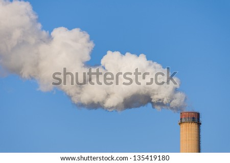 smokestack releasing pollution on clear blue sky - easy to create mask - stock photo