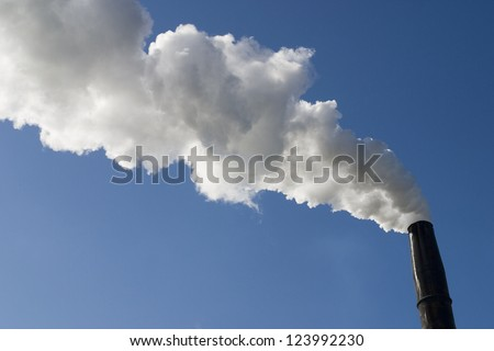 Smokestack with pollution billowing out against blue sky - stock photo