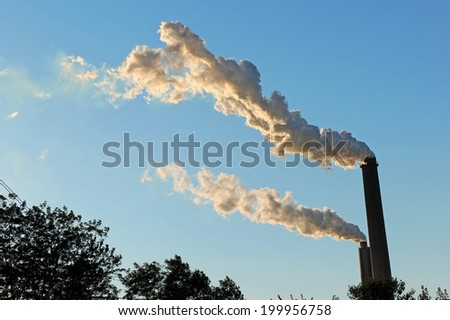 Smokestacks emitting smoke during late afternoon - stock photo
