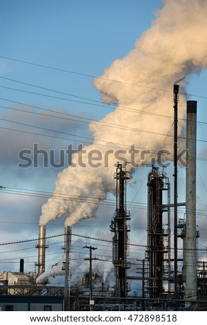 Smokestacks from oil refinery releasing thick smoke into the atmosphere