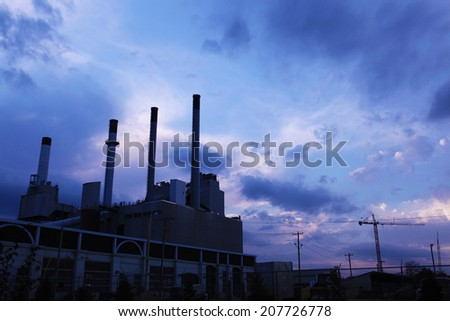 Smokestacks silhouetted in the blue and purple light of dusk