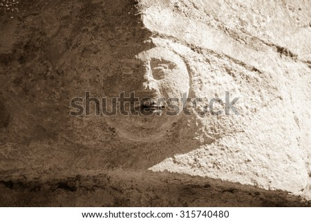 Smoking addiction. Stone human face (old building architectural detail) with real cigarette in the mouth. Aged photo. Sepia. - stock photo