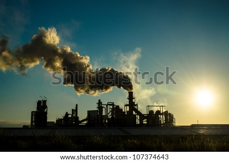 Smoking chimney  at sunset on industrial buildings complex.