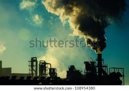 Smoking chimney  at sunset on industrial buildings complex. - stock photo