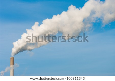 smoking chimney of a power plant against a blue sky