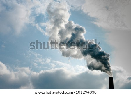 smoking chimney of a power plant against a blue sky - stock photo