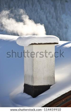 Smoking chimney of a Swiss cottage - stock photo