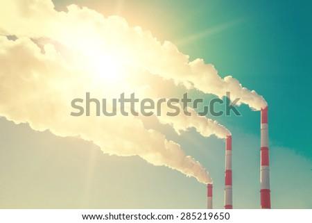 Smoking chimneys against the blue sky - stock photo